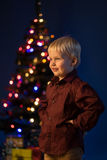 Little boy decorates the Christmas tree. Spruce with decorations. Kid and adornment. Multicolor spruce with decorations and lights bokeh. Child and gifts under royalty free stock image