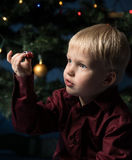 Little boy decorates the Christmas tree. Spruce with decorations. Kid and adornment. Kid and multicolor spruce with decorations and lights bokeh. Little boy and stock photos