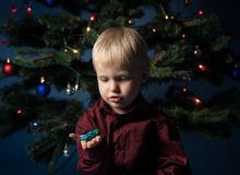 Little boy decorates the Christmas tree. Spruce with decorations. Kid and adornment. Kid and multicolor spruce with decorations and lights bokeh. Little boy and royalty free stock photos