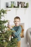 Little boy decorating christmas tree with toys and balls. Cute kid preparing home for xmas celebration. The concept of Christmas royalty free stock image