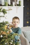 Little boy decorating christmas tree with toys and balls. Cute kid preparing home for xmas celebration. The concept of Christmas royalty free stock photos