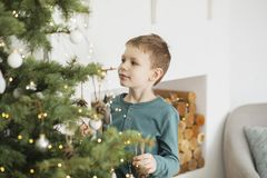 Little boy decorating christmas tree with toys and balls. Cute kid preparing home for xmas celebration. The concept of Christmas royalty free stock photo