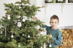 Little boy decorating christmas tree with toys and balls. Cute kid preparing home for xmas celebration. The concept of Christmas stock images