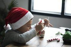 Little boy decorating a snowman marshmallow Stock Photography