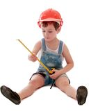 The little boy in denim shorts. Sitting on the floor in stroitelnyi helmet and is considering building roulette-isolated on white background Stock Images