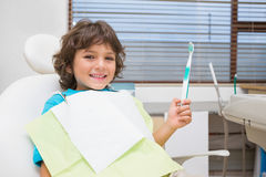Little boy in dentists chair holding toothrbrush Royalty Free Stock Photos