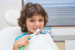 Little boy in dentists chair using toothrbrush Stock Image