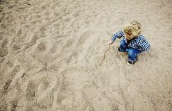 Little Boy dessinant dans le sable photos libres de droits