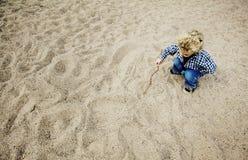 Little Boy dessinant dans le sable Photos libres de droits