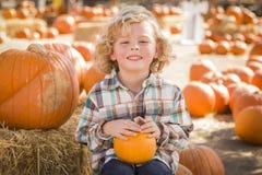 Little Boy die en Zijn Pompoen zitten houden bij Pompoenflard Stock Fotografie