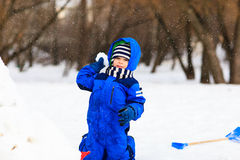Little boy dig and play in winter snow Stock Photos