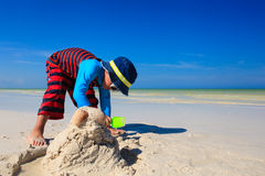 Little boy digging sand on tropical beach Royalty Free Stock Photography