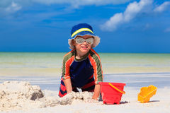 Little boy digging sand on tropical beach Stock Photo