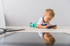 Little boy with digital gadgets in studio. Having fun with my phone. Cropped shot of cute little boy lying on floor and using mobile phone against grey wall Royalty Free Stock Photos