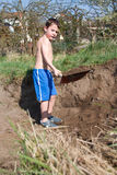 Little boy digs a hole Stock Image