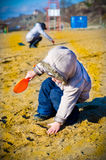 Little boy digs in sand. On a beach a shovel with mum Royalty Free Stock Photography