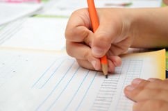 Little boy diligently writes with a pencil in his notebook. Royalty Free Stock Images