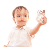 Little boy with dirty lips offers bar of chocolate Stock Image