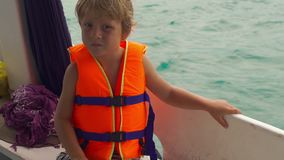 Little boy on a diving boat feel nervous before his first snorkeling in an open sea.  stock footage