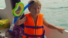 Little boy on a diving boat shows his mask and tube before his first snorkeling in an open sea. Little boy on a diving boat shows his mask and tube before his stock video