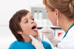 Little boy at the doctor. Say aaah - little boy at the physician checking his throat Royalty Free Stock Image