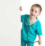 Little boy in doctor suit behind blank banner isolated Stock Image