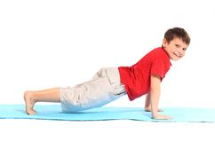 The little boy does exercise. Stock Photos