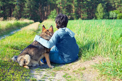 Little boy with dog on the meadow. Little boy sitting with his dog on the meadow back to camera Royalty Free Stock Images