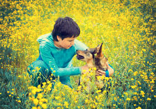 Little boy with dog on the meadow. Little boy sitting with his dog on the flower meadow Stock Photo