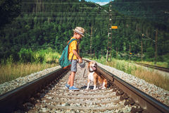Little boy with dog stay on the railwai among forest Stock Photo