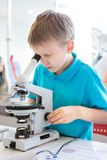 Little boy doing biochemistry research at the lab. A boy of European appearance in a T-shirt conducts biological experiments with royalty free stock photography