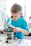 Little boy doing biochemistry research at the lab. A boy of European appearance in a blue T-shirt royalty free stock photography