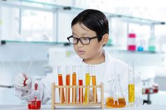 Little boy doing experiments in the laboratory. Image of a cute little boy working with chemical liquid while doing experiments in the laboratory Stock Images