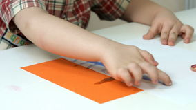 Little boy doing finger painting stock footage
