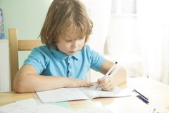 Little boy is doing his homework for elementary school.  Stock Photos
