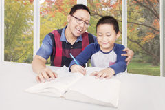 Little boy doing homework with dad Stock Images
