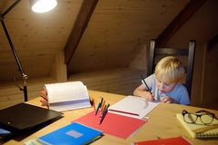 Little boy doing homework, painting and writing at home evening. Preschooler learn lessons - draw and color image. Kid training to. Write and to read. Child stock photos