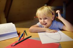 Little boy doing homework, painting and writing at home evening. Preschooler learn lessons - draw and color image. Kid training to. Write and to read. Child stock image