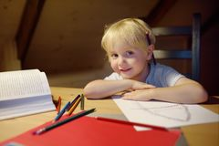 Little boy doing homework, painting and writing at home evening. Preschooler learn lessons - draw and color image. Kid training to. Write and to read. Child stock photo