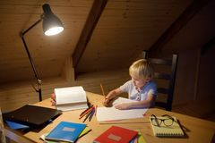 Little boy doing homework, painting and writing at home evening. Preschooler learn lessons - draw and color image. Kid training to. Write and to read. Child royalty free stock photos
