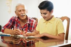 Little Boy Doing School Homework With Old Man At Home. Happy little boy doing school homework with old men at home. Family relationship between grandfather and Royalty Free Stock Image