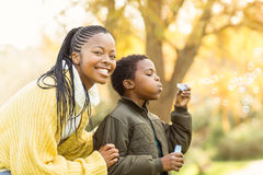 Little boy doing some bubbles with his mother. On an autumns day Royalty Free Stock Photography