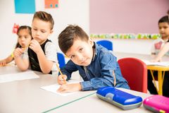 Little boy doing some math at school. Portrait of a Hispanic little boy doing some basic math exercises in preschool and making eye contact Royalty Free Stock Images