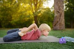 Little boy doing stretch during workout outdoors stock image
