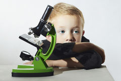 Little boy don't want to study.sad child.children.microscope.Education. Little boy don't want to study.sad child.children.Schoolboy with a microscope.Smart boy Stock Images