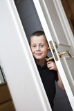 Little Boy by the door. Little Boy looking out from the Closet stock photo