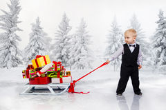 Little boy drags a huge heap of Christmas gifts Stock Photo