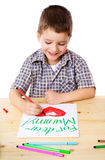 Little boy draw for mum. Smiling little boy at the table draw with crayons for mum,  on white Stock Photos
