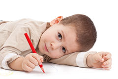 Little boy drawing. Litle boy drawing with red pencil Stock Photography