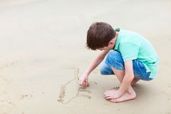 Little boy drawing at beach Stock Image